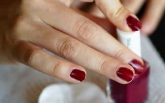 pose de son vernis a ongles rouge