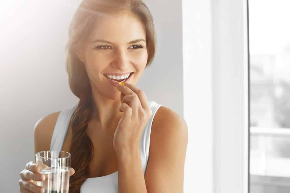 femme qui prend un complement alimentaire avec de l'eau