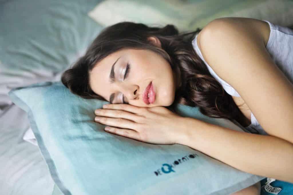 Une femme endormi utilisant un réveil lumineux