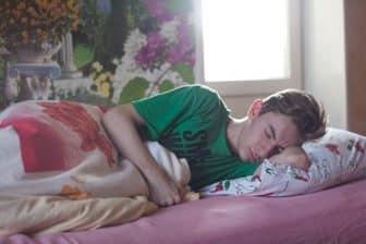 Un homme endormi qui utilise un réveil lumineux